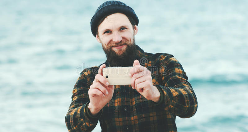 Bearded Man taking selfie using Smartphone at sea. Travel Fashion Lifestyle and modern technology concept happy smiling emotions royalty free stock images