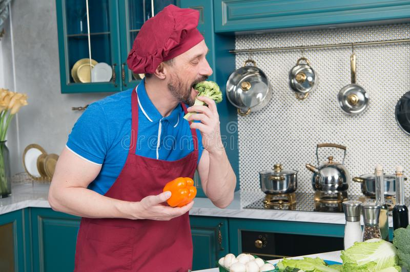 Bearded Man taste fresh broccoli and paprika before cooking at kitchen. Man loves vegetarian food concept royalty free stock photo