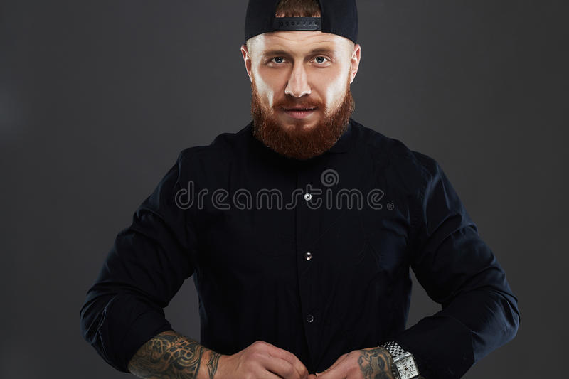 Bearded man with tattoo.old Hipster boy.brutal.cap. Bearded man with tattoo.old Hipster boy.brutal handsome man in cap royalty free stock images