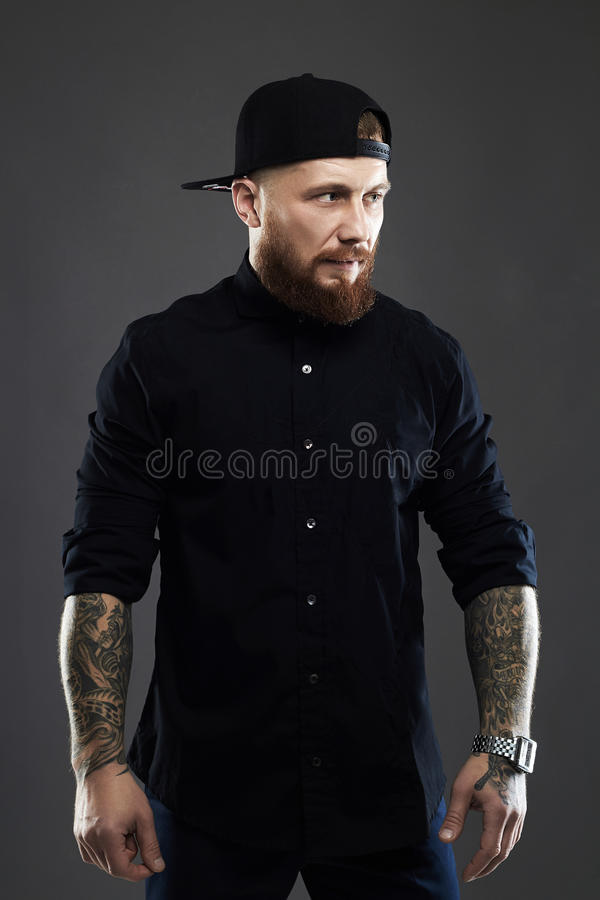 Bearded man with tattoo. Old Hipster boy.brutal handsome man in cap stock images