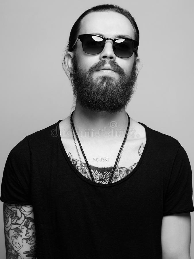 Bearded man with tattoo and sunglasses. Fashionable handsome man with tattoo and sunglasses. Brutal bearded boy in trendy glasses stock image