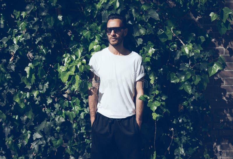 Bearded man with tattoo wearing blank white tshirt and black sunglasses.Green garden wall background. Horizontal mockup royalty free stock photo