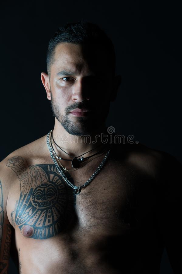 Bearded man with tattooed chest. Man with muscular torso. Fit model with tattoo design on skin. Sportsman or stock photography