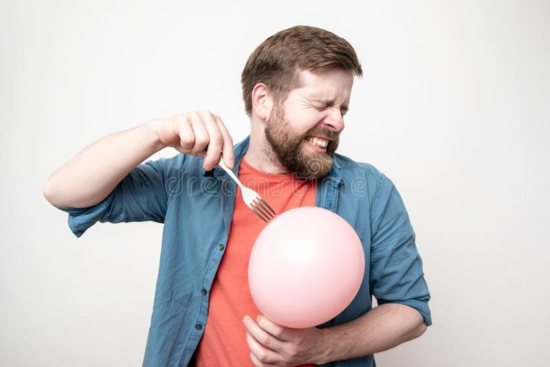 Bearded man is about to burst a balloon with a fork and bared his teeth in fear. Fun or stress concept stock image