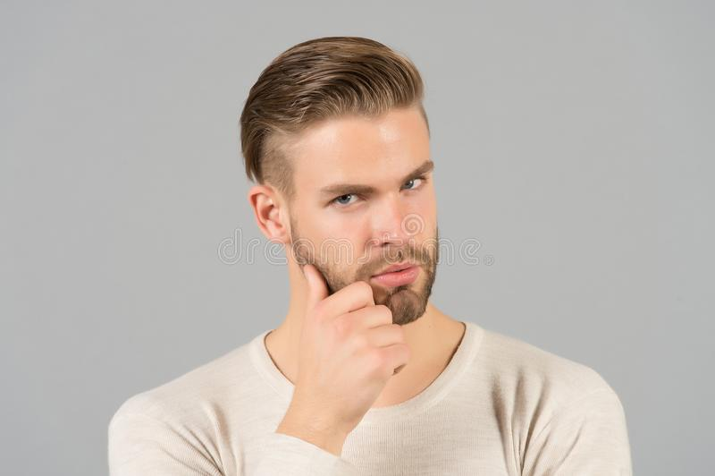Bearded man touch beard with hand. Macho with stylish hair and healthy young skin. Guy with unshaven face and mustache. Beard groo. Ming and hair care in stock images