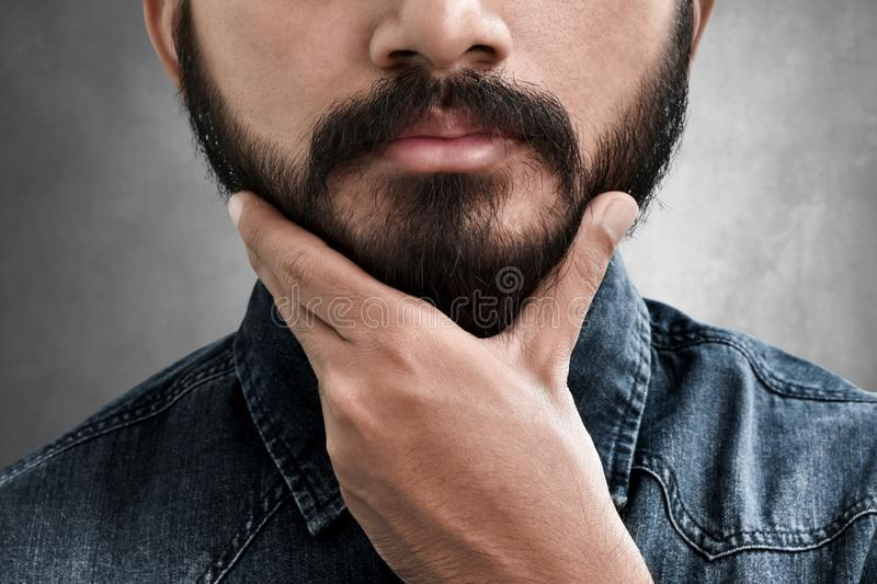 Bearded man touching his beard royalty free stock photo