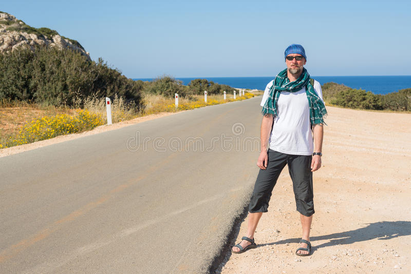 Bearded man traveling hitchhiking. Bearded man, wearing a scarf, traveling hitchhiking, is on the road to the sea. Sunny morning on Cyprus royalty free stock photo