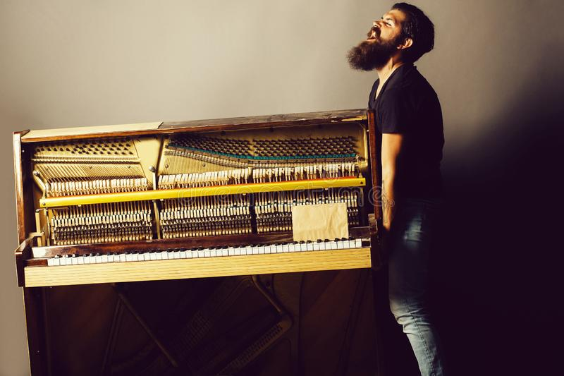Bearded man trying to move wooden piano. Handsome bearded strong man with stylish hair mustache and beard trying to move old wooden or wood open piano with royalty free stock photography