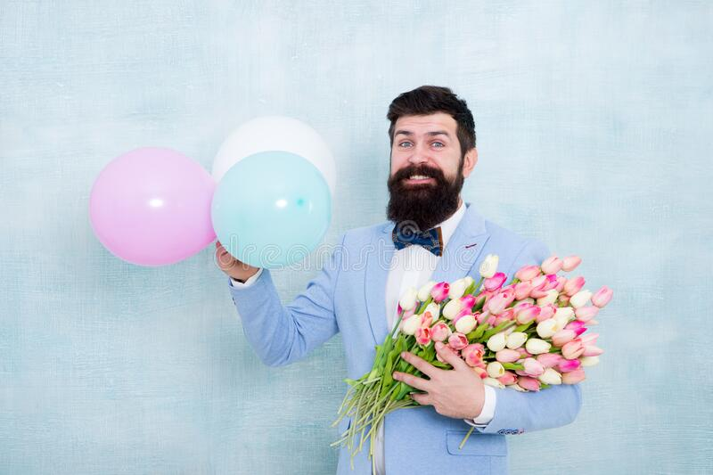 Bearded man with tulips. Guy with air balloons. Birthday party. Bearded man hipster with flower bouquet. Womens day stock photo