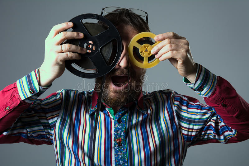 Bearded man with two 16mm film reel royalty free stock images