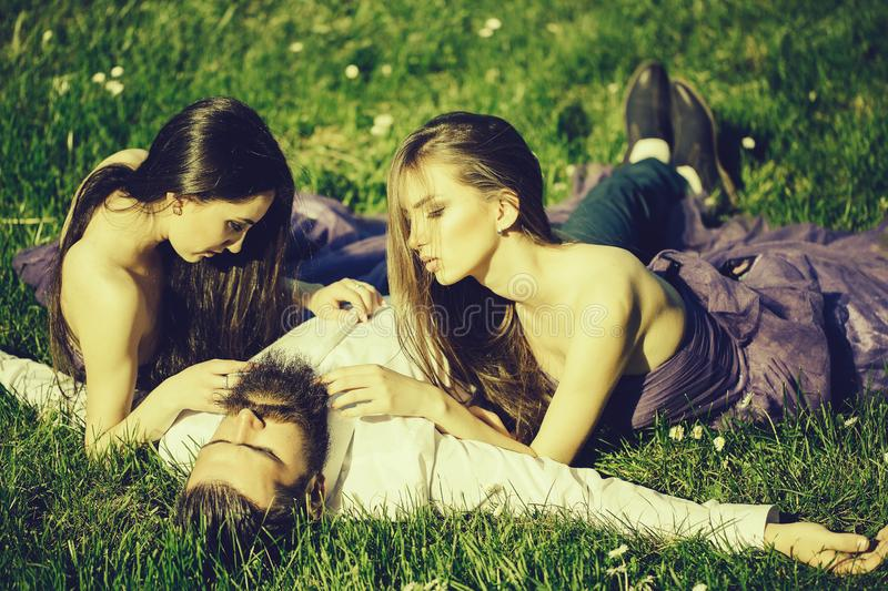 Bearded man and two women on grass royalty free stock photography