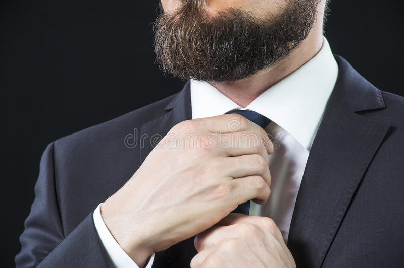 Bearded man tying up his necktie stock images