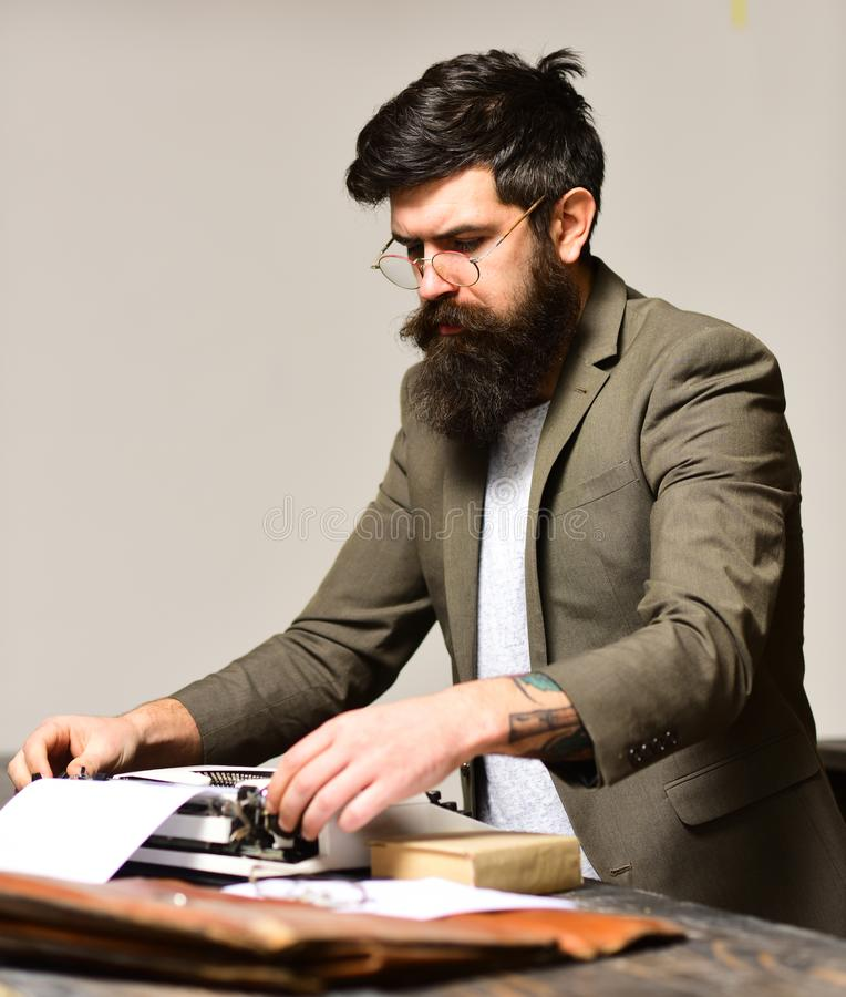 Bearded man type on typewriter. Man with long beard and mustache typewrite research paper. Businessman in suit work as stock photography