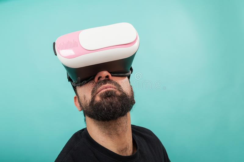 Bearded man use virtual reality glasses, goggles. Guy in VR headset is looking at interactive screen. Playing mobile game app on. Man use virtual reality glasses royalty free stock image