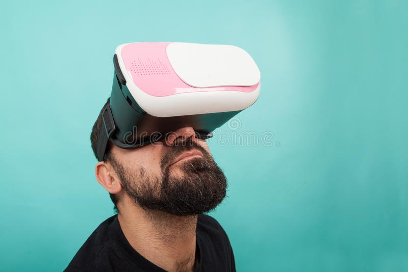 Bearded man use virtual reality glasses, goggles. Guy in VR headset is looking at interactive screen. Playing mobile game app on. Man use virtual reality glasses stock images