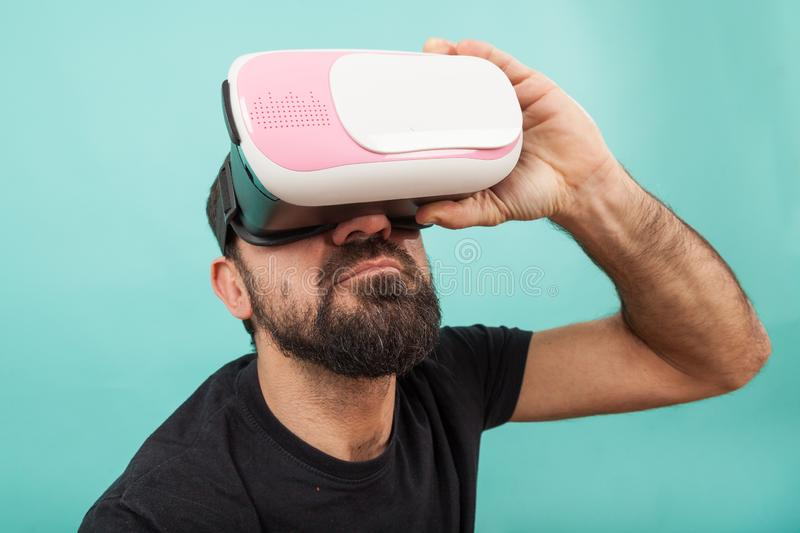 Bearded man use virtual reality glasses, goggles. Guy in VR headset is looking at interactive screen. Playing mobile game app on. Man use virtual reality glasses royalty free stock images
