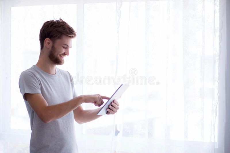 bearded man using tablet while standing royalty free stock image