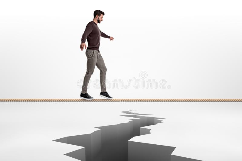 A bearded man is very concentrated when walking on a tight rope above a crack in the earth. royalty free stock photos
