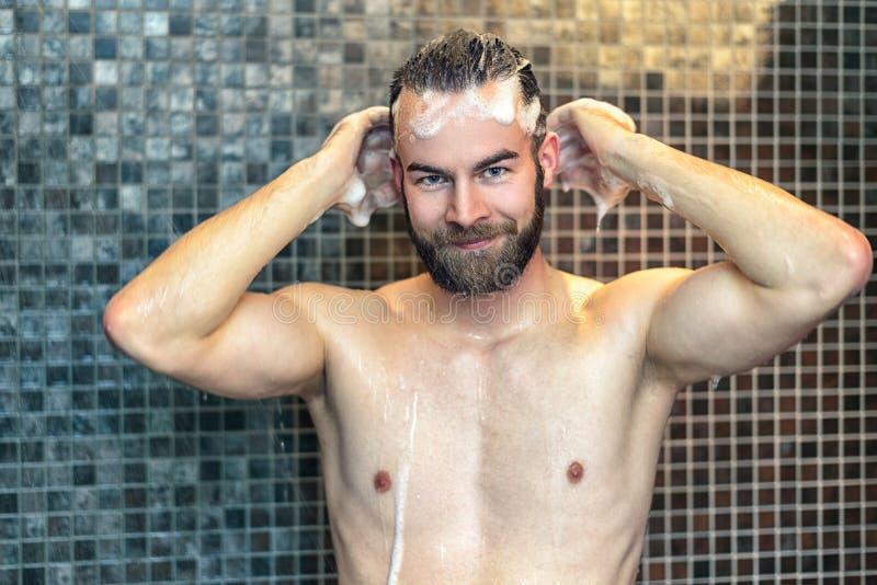 Bearded man washing his hair with shampoo stock image