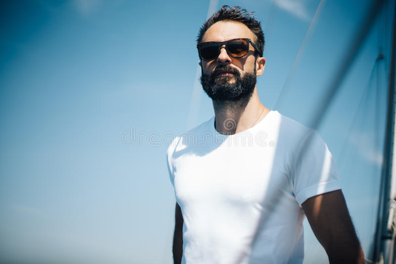 Bearded man wearing sunglasses, standing on a royalty free stock image