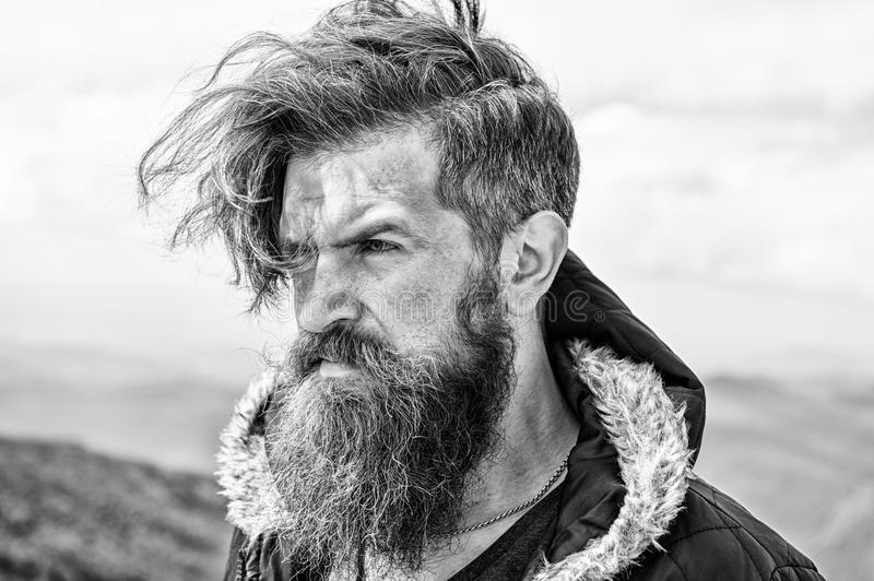 Bearded man on windy mountain top on natural cloudy sky stock image