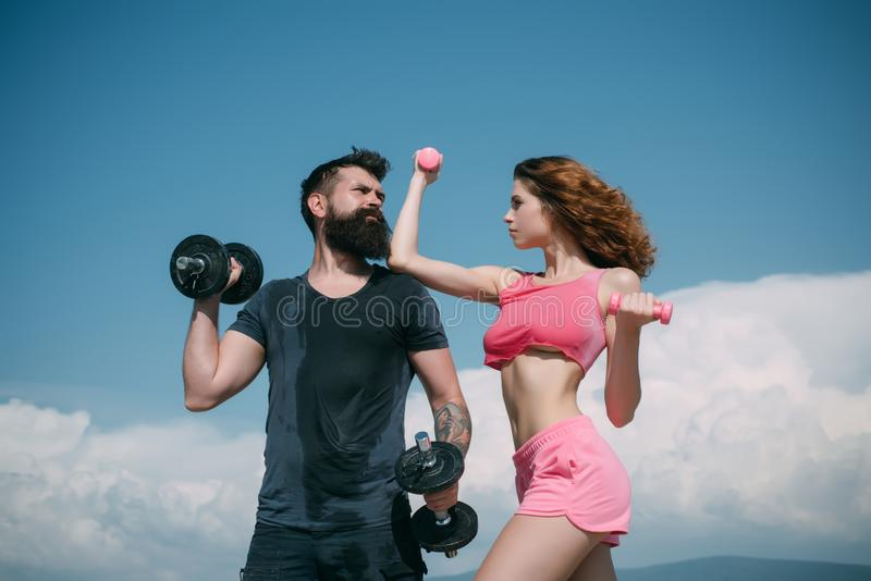 Bearded man and woman with fit belly. healthy lifestyle. dieting. freedom. dumbbell lifting. sport and fitness. sporty stock photo
