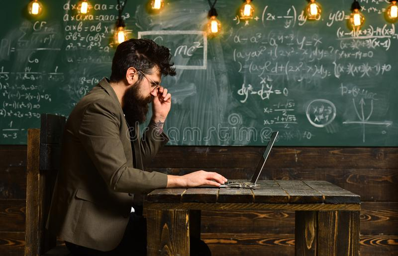 Bearded man work on laptop in classroom. Bearded man with long beard with computer on chalkboard, new technology concept royalty free stock photos