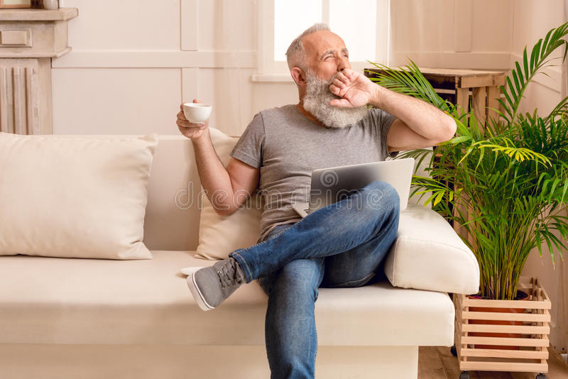 Bearded man yawning with coffee cup and laptop while sitting on sofa at home stock image