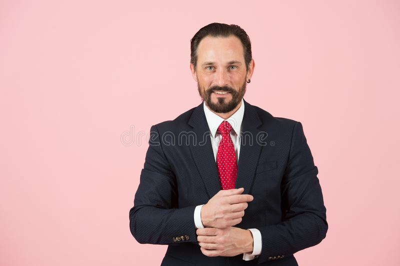 Bearded manager in blue suit isolated on pink background. Handsome aged businessman in black suit is looking at camera and smiling royalty free stock images