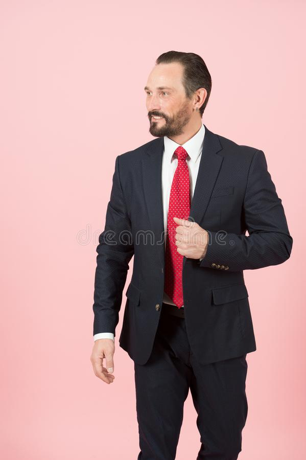 Bearded manager holds hand on flap of blue suit jacket wearing red tie on white shirt isolated over pink background royalty free stock photos