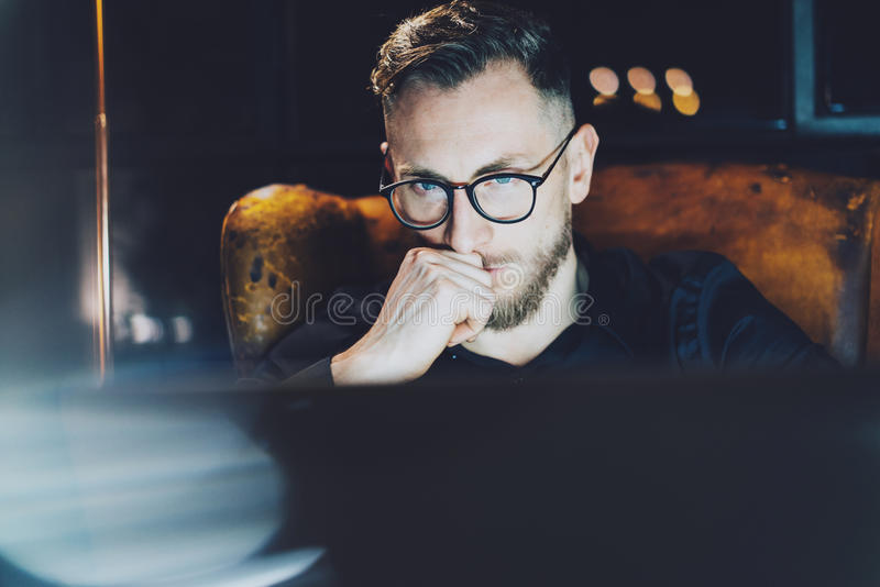 Bearded manager working modern loft office. Man sitting in vintage chair at night,thinkig new startup project.Using stock images