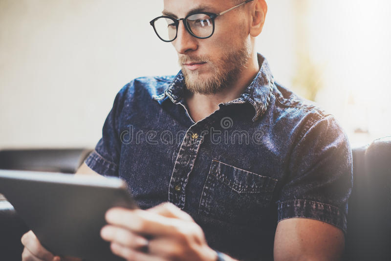 Bearded manager working tablet device modern Interior Design Loft Building.Man relax Vintage sofa use contemporary royalty free stock photography