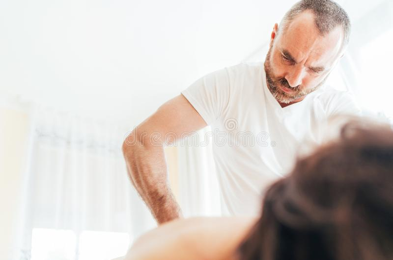 Bearded Masseur man doing massage manipulations on the low back area during young female body massaging. Health care concept image royalty free stock photo