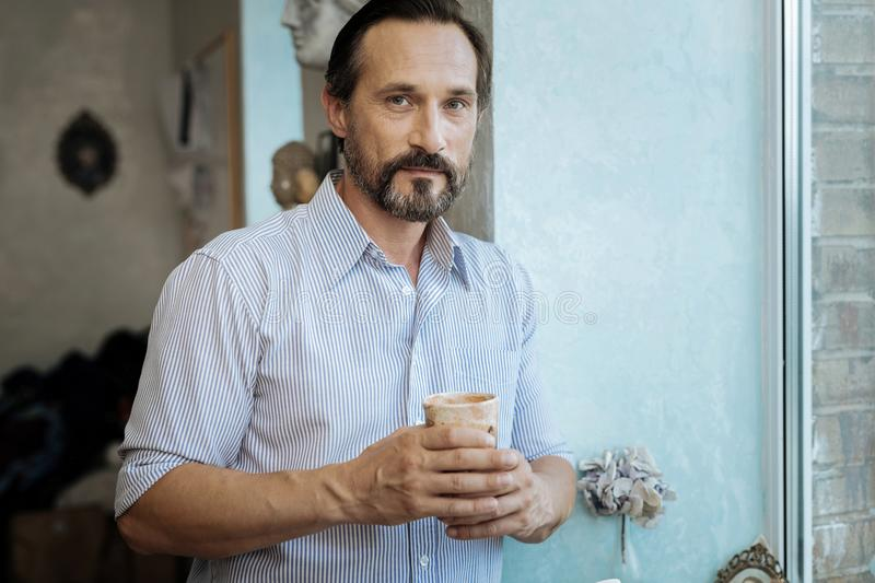 Bearded mature man holding cup with hot tea royalty free stock photo