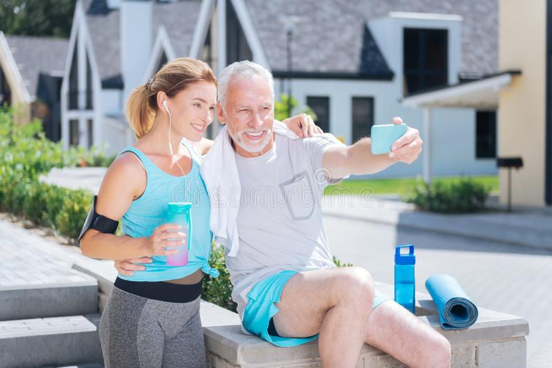 Bearded mature man holding his blue phone while making selfie with wife stock image