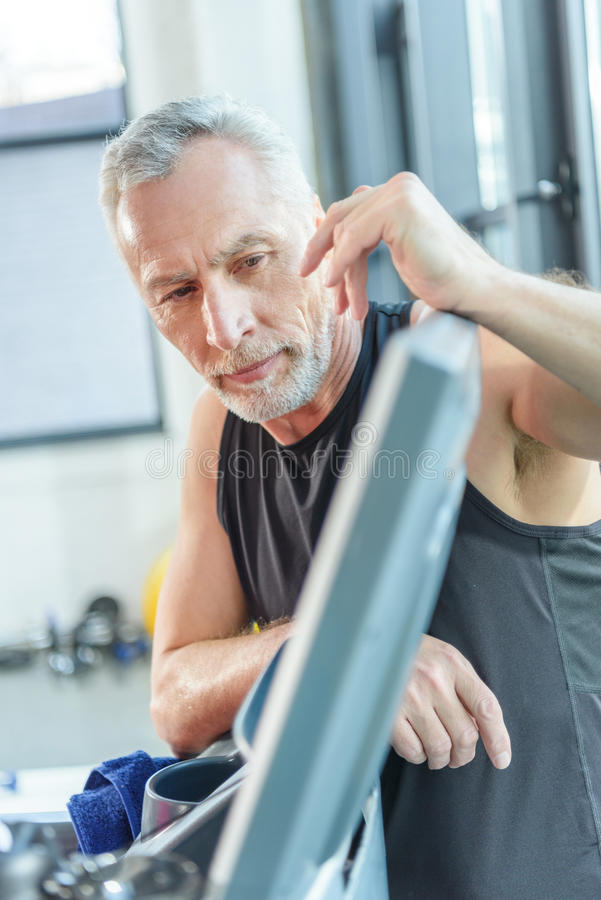 Bearded mature man leaning at equipment in gym royalty free stock photos