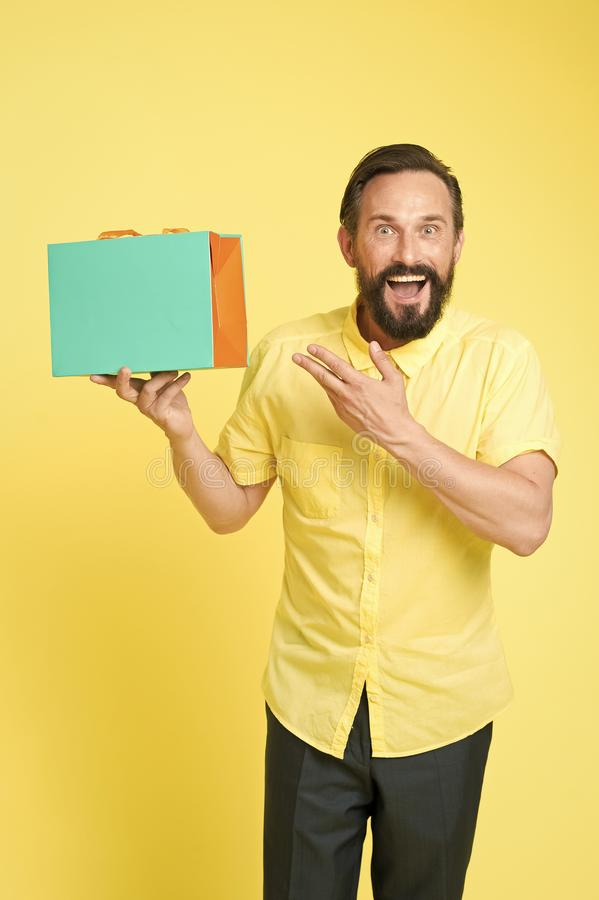 Bearded mature man with shopping bag on yellow background. Sale and discount. Online shopping. Profitable purchase. Shop. Assistant or sales expert. Shopping stock images
