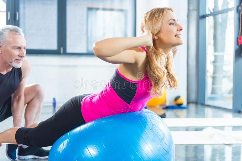 Bearded mature man training woman doing abs on fitness ball royalty free stock photo