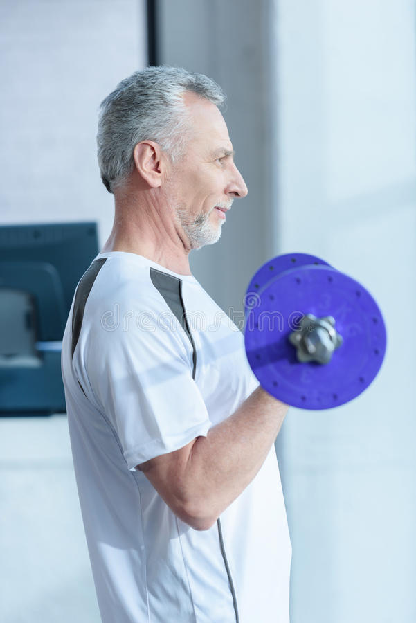 Bearded mature sportsman training with barbell in gym stock photo