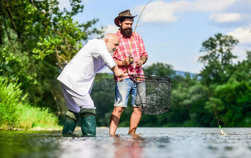 Bearded man and brutal hipster fishing. Family day. Fishing team. Friends catching fish. Hobby and recreation. Catching royalty free stock image