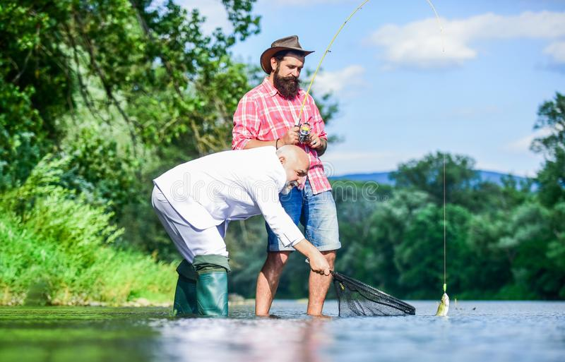 Bearded man and brutal hipster fishing. Fishing team. Active day. Family day. Hobby and recreation. Catching fish with royalty free stock photography