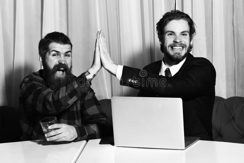 Bearded men, businessmen with glass of whiskey, laptop and phone stock images