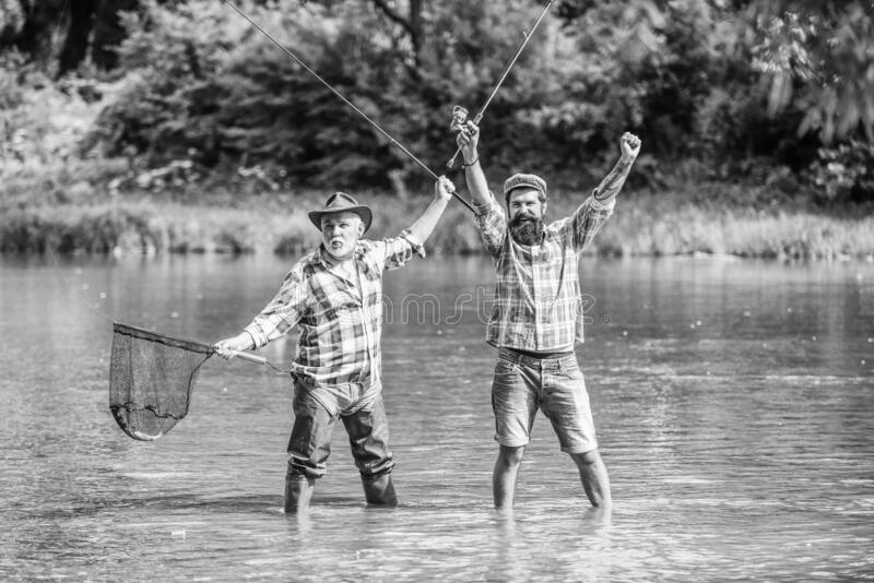 Bearded men catching fish. Master baiter. Mature man with friend fishing. Summer vacation. Happy cheerful people stock photos