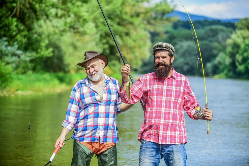 Bearded men catching fish. Mature man with friend fishing. Summer vacation. Happy cheerful people. Family time stock image