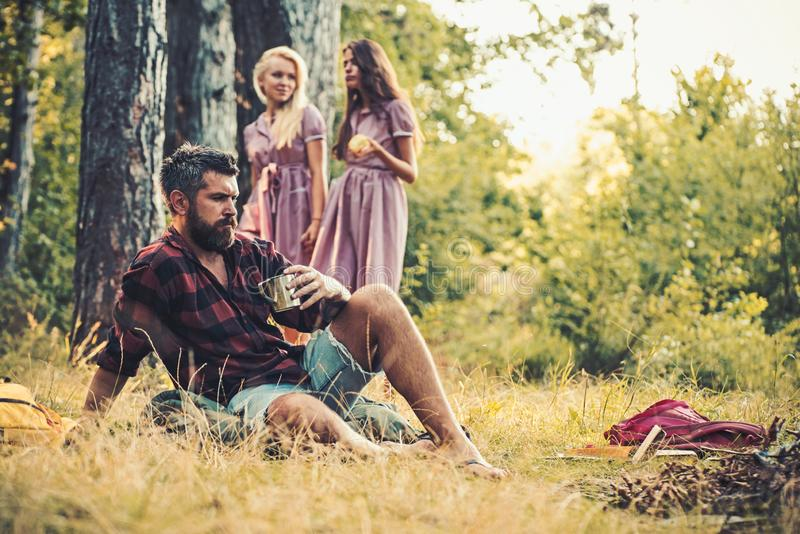 Bearded man drink tea at bonfire with women on blurred background. Hipster with beard sit at campfire. Friends enjoy royalty free stock photos