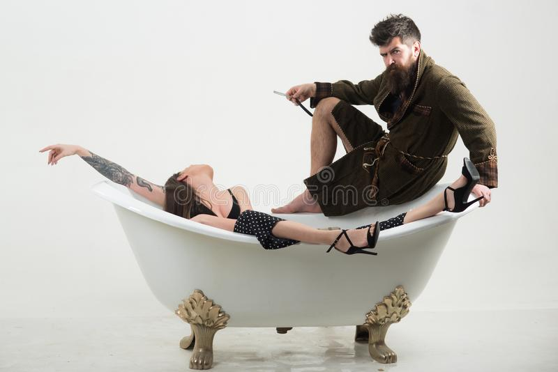 Bearded man hold shaving razor. Man with bearded face enjoy bath with sensual woman. Bearded man with unshaven face royalty free stock image