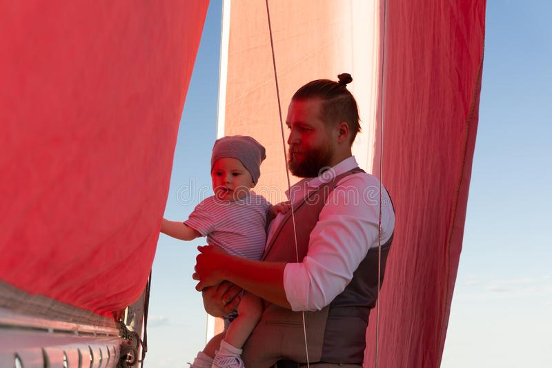 Man with a child on a sailing ship stock photography
