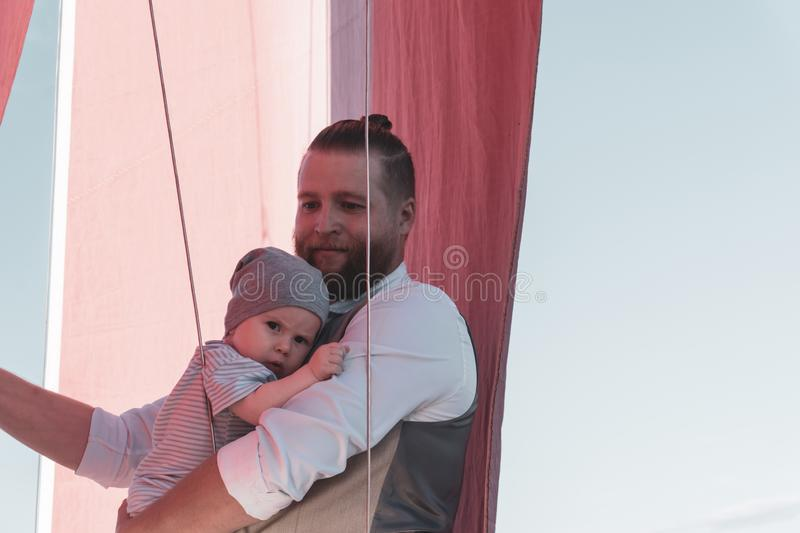 Man with a child on a sailing ship stock photo