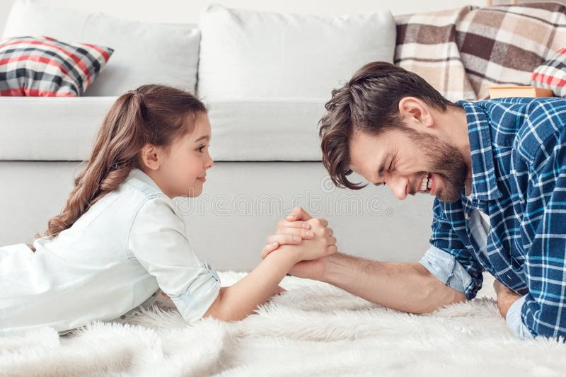 Father and little daughter at home lying on floor doing arm wrestling having fun. Bearded men and little girl at home family time lying on carpet on floor doing stock images