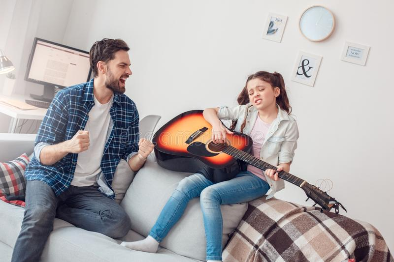 Father and little daughter at home sitting girl playing guitar singing having fun royalty free stock images
